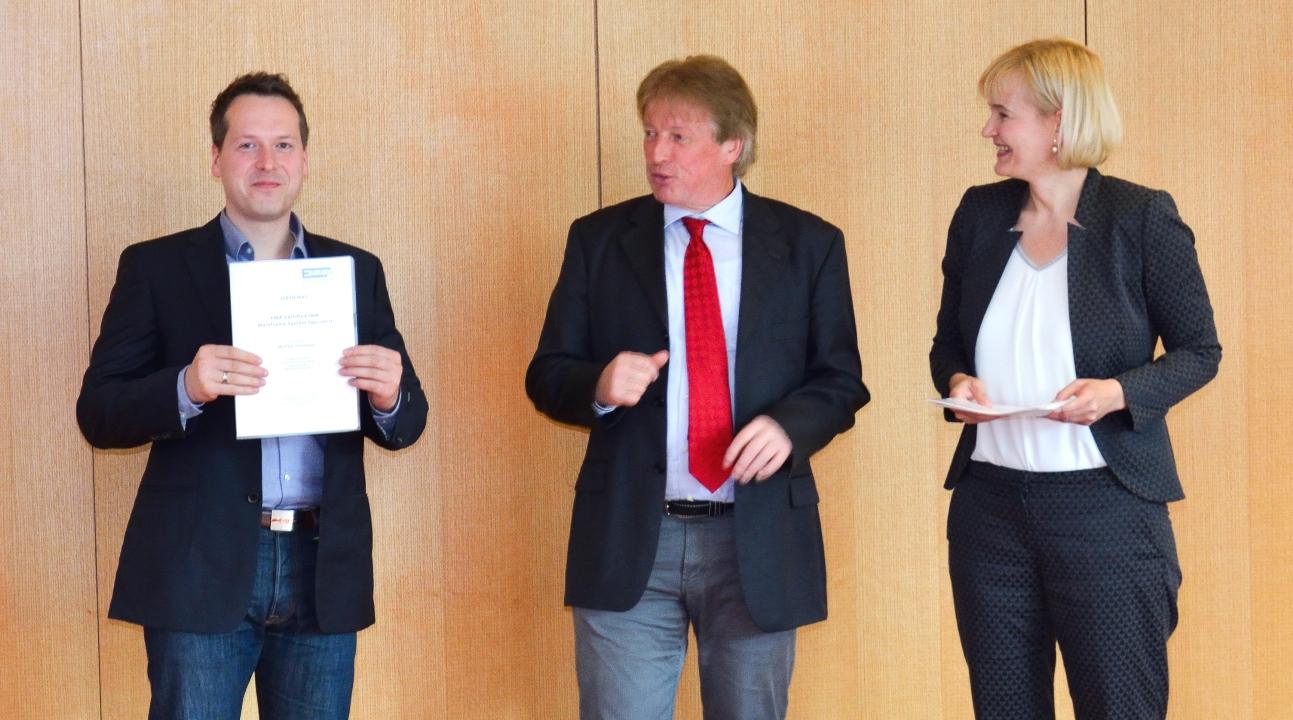 "Michael Jünemann erhäalt das Zertifikat zum ""EMA IBM Mainframe Specialist. Mitte: , rechts: Gitta Demohn Geschäftsfühererin von FI-TS"